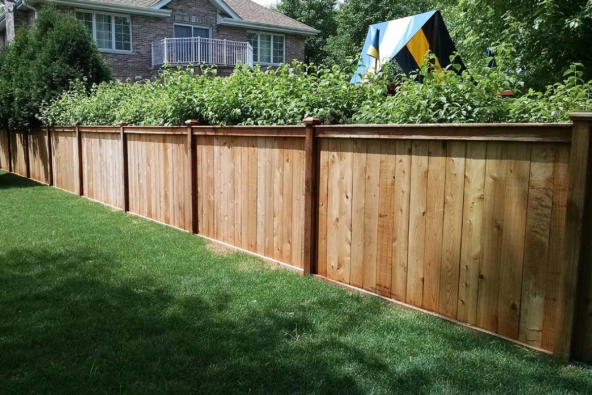 Traditional Wood Fence With A Custom Top Rail Designed And