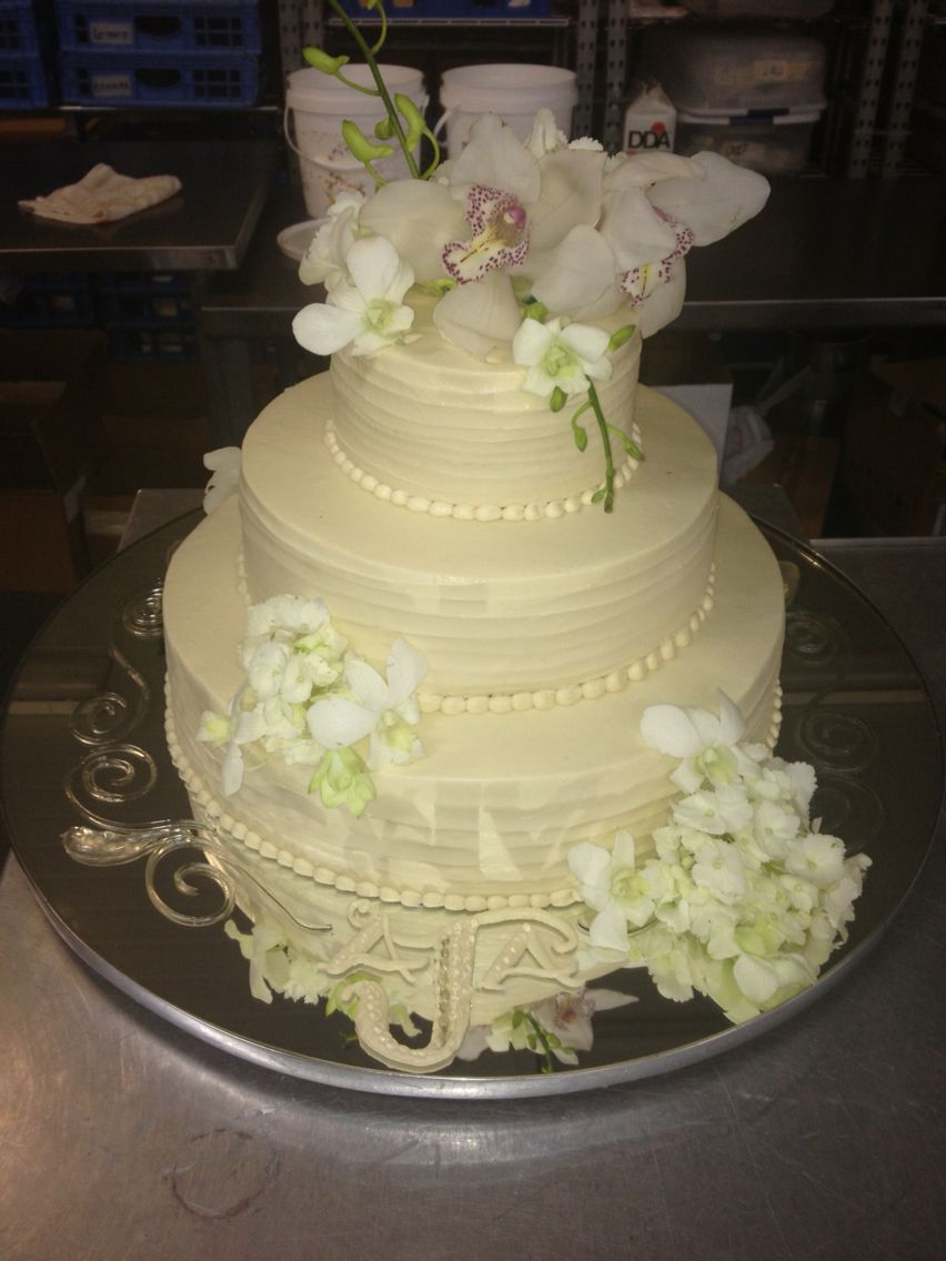 Three tiered cream colored wedding cake iced in rustic looking ...