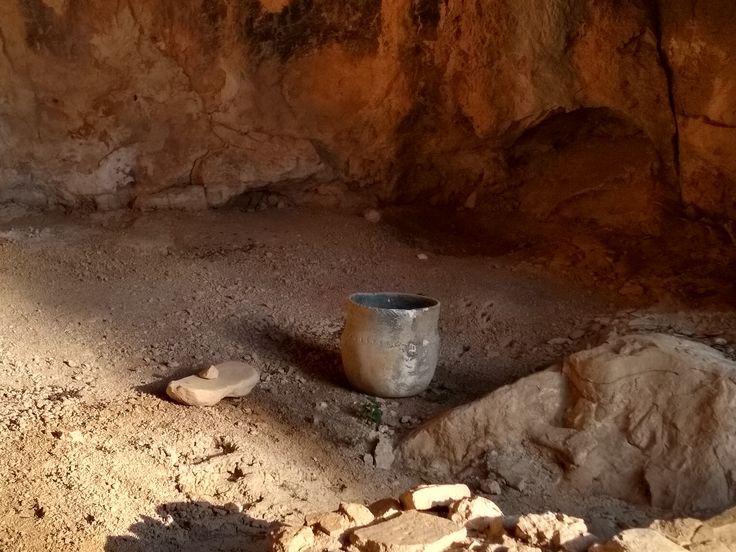 Se ven al fondo las dos cavidades de los silos, más cerca encontramos una vasija y una piedra empleada para moler grano