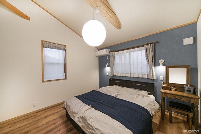 寝室は屋根の形状を活かした斜め天井 ブルーの色調で 落ち着いた