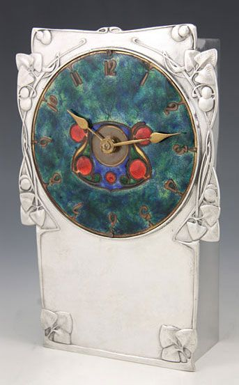 Polished pewter clock with wonderful large enamelled dial surrounded by typical (George) Knox decoration; England, c.1905.