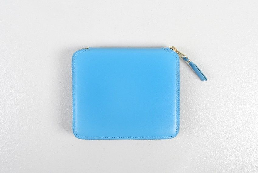 large classic wallet blue - Large classic zip around leather wallet in blue by Comme des Garçons. Soft full grain leather exposed gold tone zipper fastening. Features four credit card pockets, a billfold compartment, and a coin pouch with snap closure.   Measures 4.75 W x 4.25 H    100% cow hide   Made in Spain