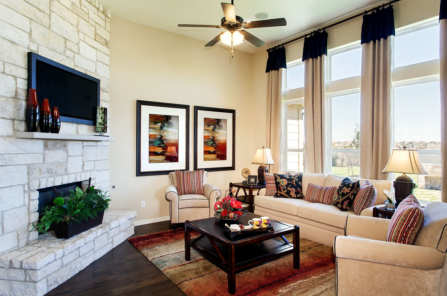 Cozy family room with large windows and a stone fireplace ...