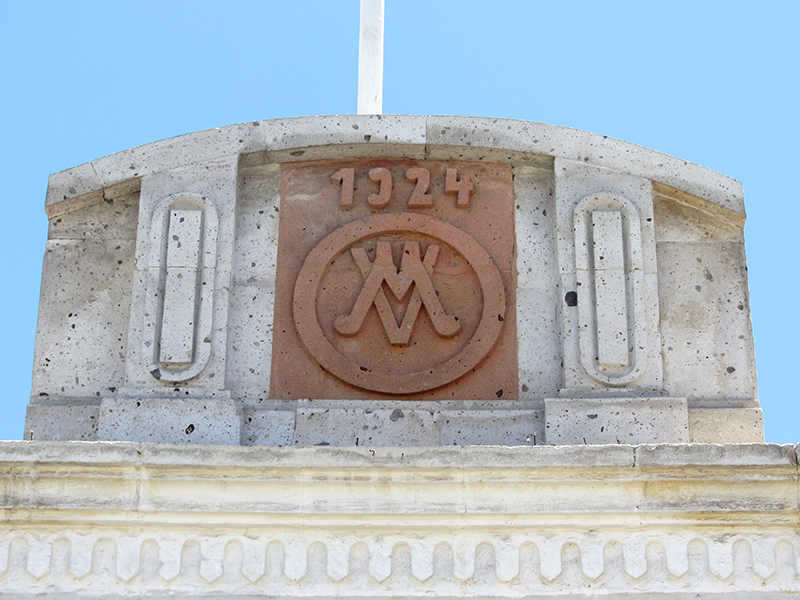 Cacería Tipográfica N° 331: El año de construcción 1924 junto al monograma MV ambos tallados en sillar rojo en una fachada de la calle Cortaderas en Yanahuara, Arequipa.