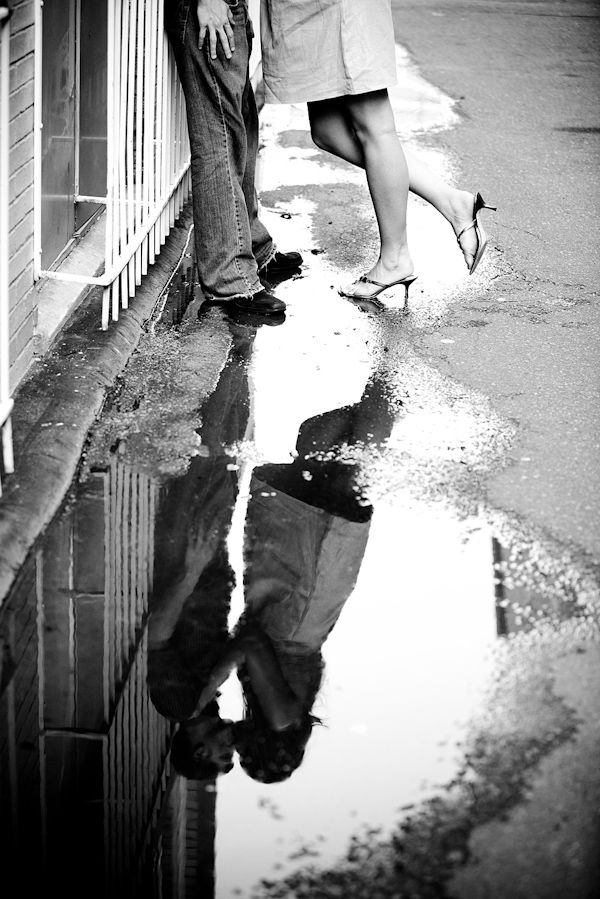 black and white photo - fun perspective of the happily engaged couple kissing in the reflection of a puddle - photo by North Carolina based wedding photographers Cunningham Photo Artists
