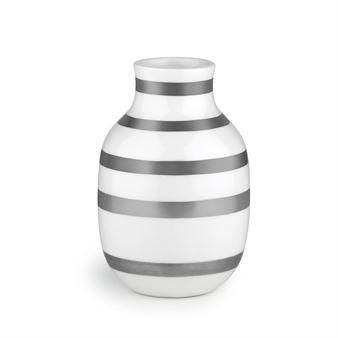 Kählerin hopeanvärisessä Omaggio-maljakossa yhdistyvät kaksi tämän hetken suosituinta materiaalia: keramiikka ja metalli. Omaggion ovat suunnitelleet Jelena Schou Nordentoft ja Ditte Reckweg, ja siitä on tullut moderni designikoni. Tässä versiossa maljakkoa koristavat tyylikkäät hopearaidat, joissa on havaittavissa myös vaaleanpunaisen, vihreän ja violetin sävyjä. Kylmän hopeiset raidat tuovat kivan kontrastin maljakon pyöreisiin muotoihin ja antavat sille kauniin feminiinisen ilmeen.