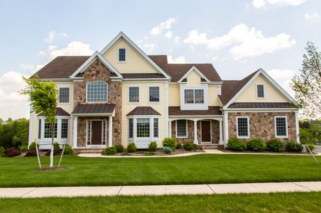 Stone Accents And White Pillars Contrast With Pale Yellow Siding The Bedminster New Homes By Fallone Group The Hamp House Exterior Stone Houses House Siding