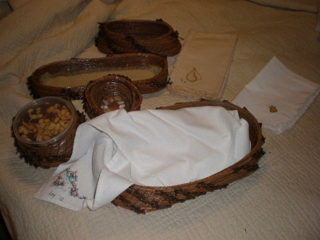 Pine needle bread basket with cross stitched bread cloth, cracker basket and nut bowl.