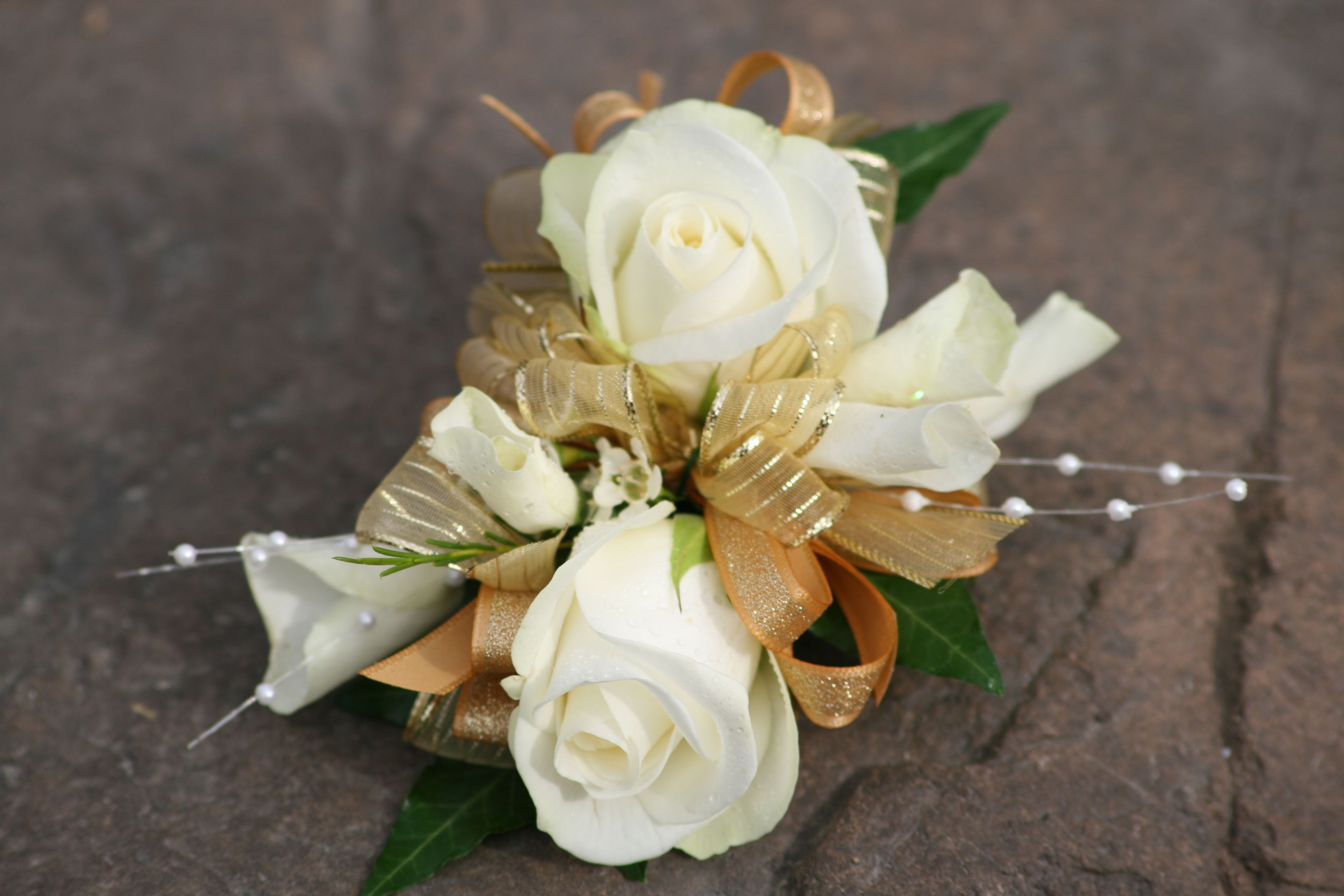 White rose corsage with gold ribbonese flowers are professionally white rose corsage with gold ribbonese flowers are professionally arranged by florists in a izmirmasajfo Choice Image