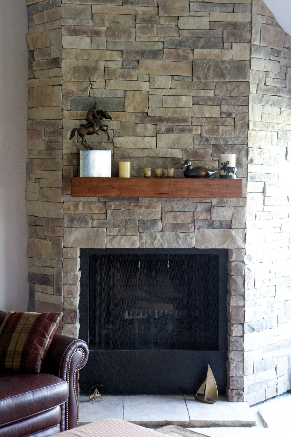 ledge stone fireplace installed over drywall with a spruce beam wood mantel stained in shaker maple stone veneer was installed without a mortar joint