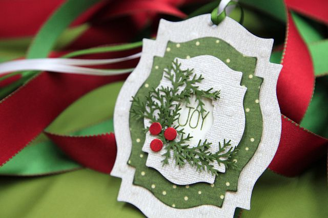 handmade Christmas tag ... also would be a gorgeous ornament ... four sizes of labels die... three for concentric layers ... one to make a window through the top two ... punched foliage and three red berry circles ... luv the negative space in the center with the word JOY down deep in the layers ... luv it!!