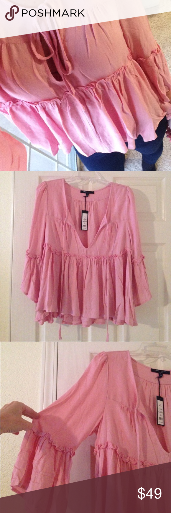 """Romeo + Juliet Couture Bohemian/Bell-sleeve Top Pretty in pink & perfect for pink October! Color is """"coral/blush"""". This top has a boho/chic vibe. Pleated & flowy w/ruffle trim; slight bell sleeves w/ruffle trim; keyhole neck w/ties. Wear it w/flared pants or skinnies & edgy shoes! Super soft. 100% viscose. 23"""" front, 26"""" back, 18"""" sleeves, 19"""" bust. Fit is good, but a little too big at keyhole front on me. There's a TEENY hole at seam near tag where security tag was removed. It's not…"""