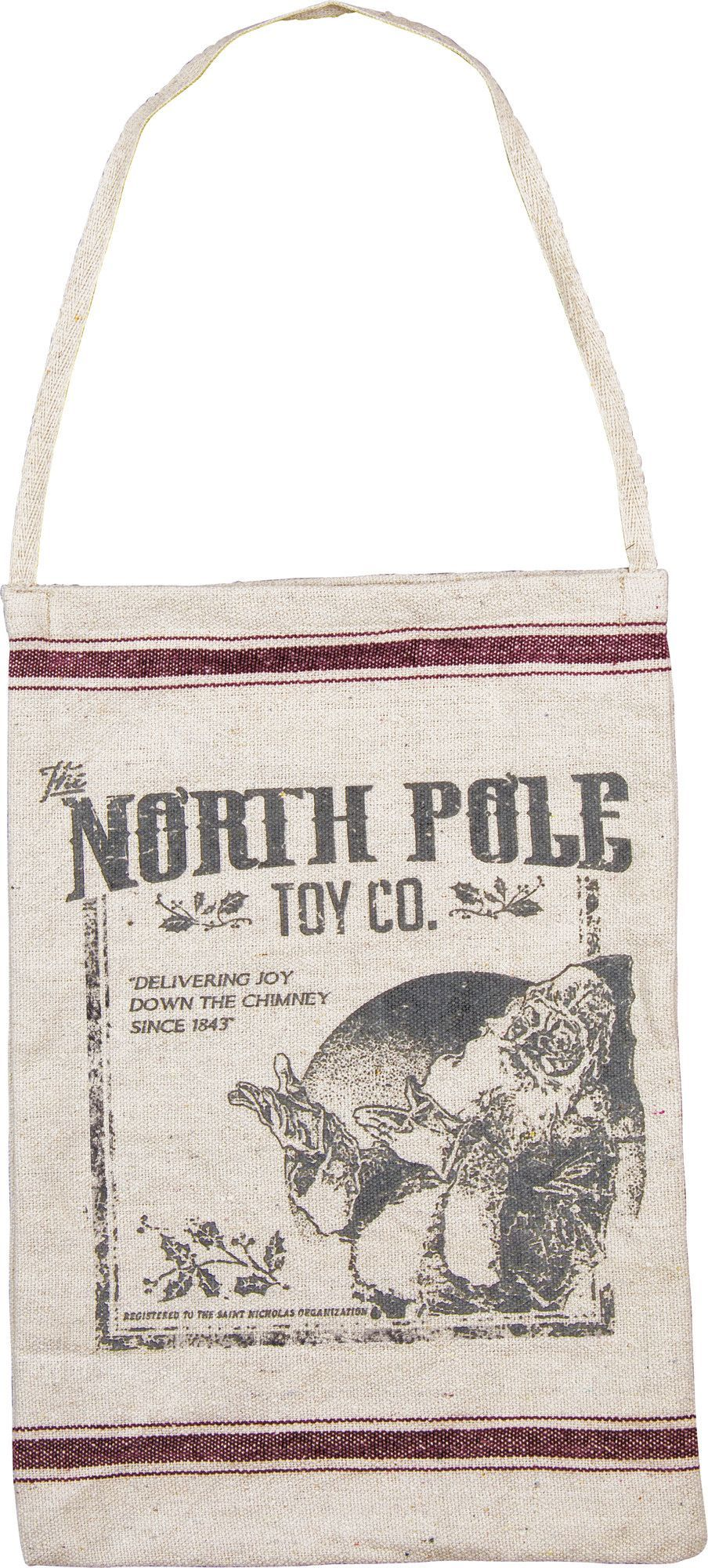 """We love this versatile North Pole Toy Company bag with weathered Christmas print. """"Delivering joy down the chimney since 1843."""" - 12"""" x 18"""". - Cotton and polyester. - Imported."""