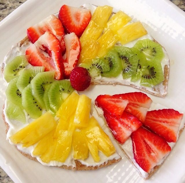 Fruit pizza: tortilla, yogurt, strawberries, kiwis, pineapples, and a drizzle of honey