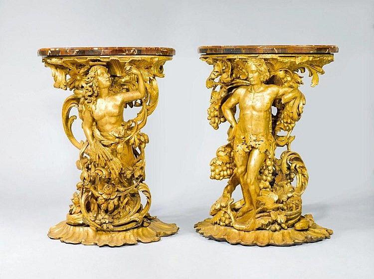 <B>PAAR FIGÜRLICH GESCHNITZTE KONSOLEN,</b></i> Spätbarock, wohl Italien, 19. Jh. <br> Holz reich geschnitzt mit Baccus bzw. Flora in Rocaillen, Blumen und Trauben auf Rocaillensockel sowie vergoldet. Halbrundes Marmorblatt. 73x37x98 cm. Eine Hand des Bacchus fehlt.  <br>    <br>  <B>PAIR OF CONSOLES DESIGNED AS FIGURES,</b></i>late Baroque, probably Italy, 19th century. <br> Wood carved as Bacchus and Flora, respectively, decorated with rocailles, flowers and grapes, and gilt. Half-round…