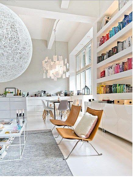Hay tantos detalles de diseño nórdico y color en este increíbleloft finlandés que uno uno sabe donde mirar. Los muebles de diseño, las estructuras de obra como la estantería rellena de libros orde…