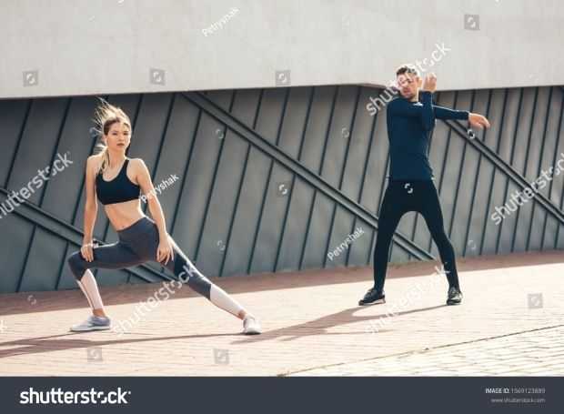 Beautiful fitness sportgirl and sportmen with fit body in sportswear exercising outdoors, stretching...