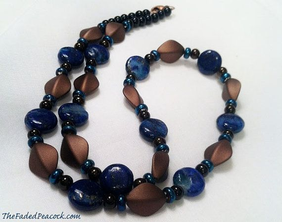 Bronze acrylic diamond and lapis lazuli by TheFadedPeacock on Etsy. The Cassandra necklace, measuring approximately 26.5 inches in length, is comprised of bronze colored acrylic diamond shaped beads, bronze glass beads, black glass beads, sapphire colored glass beads, and lapis lazuli, This necklace is secured with an antiqued copper lobster claw clasp. This is a one time only production piece. $45