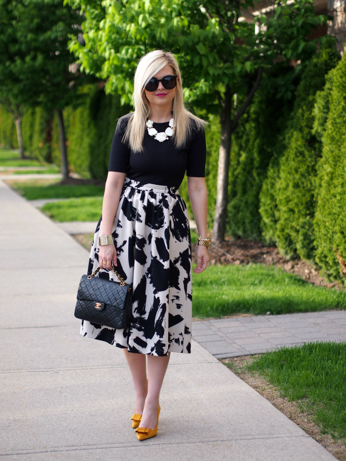 e0e9630b1f Splatter-print black and white skirt, black top, white statement necklace,  heels