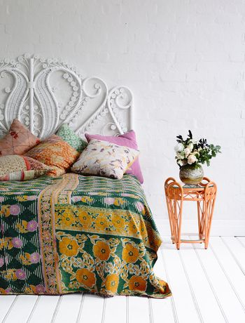 beautiful green kantha quilt, a white-washed vintage rattan headboard, quirky tangerine sidetable... perfectly boho bedroom