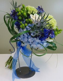 A clutch bouquet in blue and green featuring hydrangea, thistle, hypericum berries, delphinium and roses.