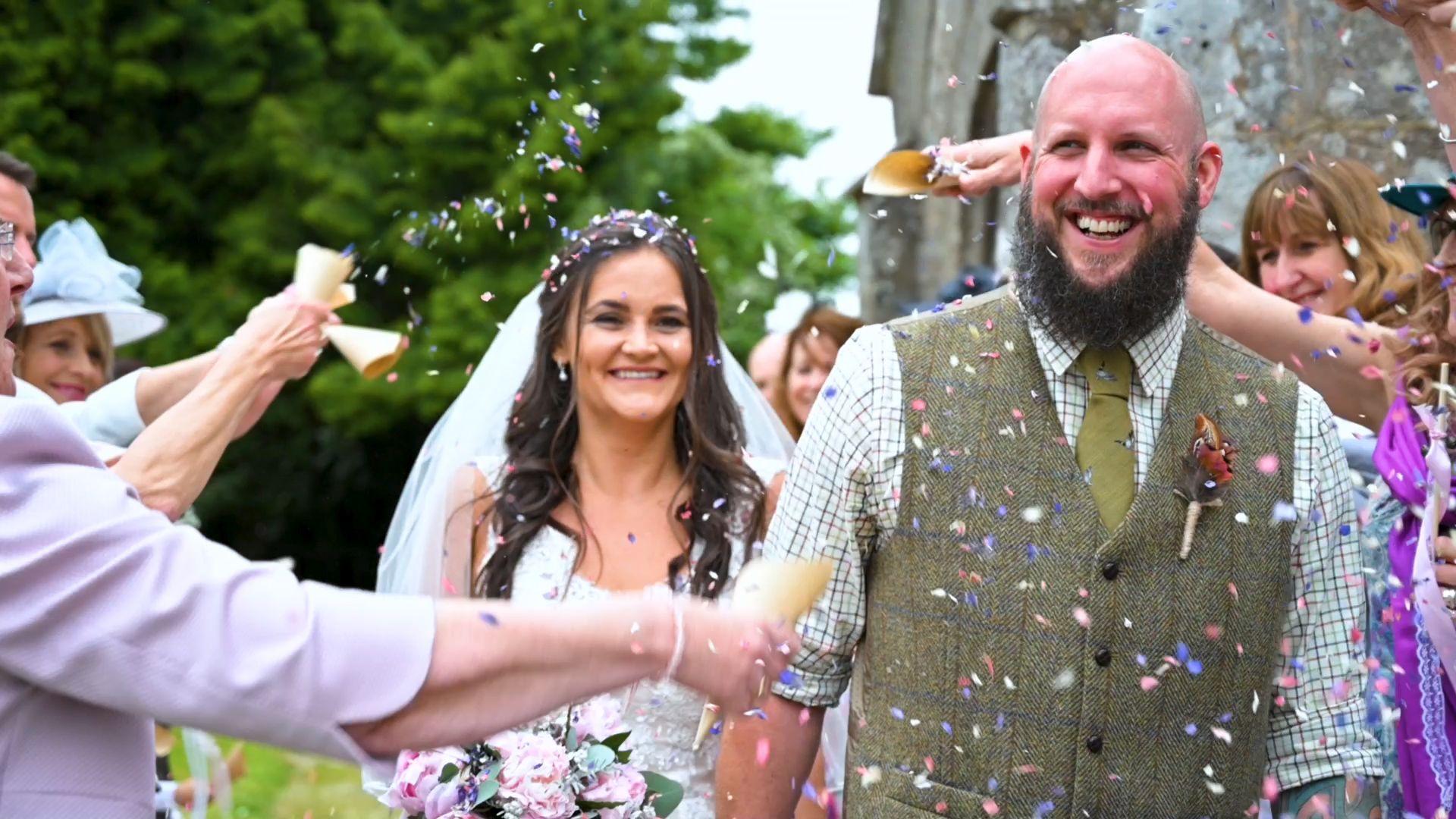 Newly wed couple walking through a confetti throw