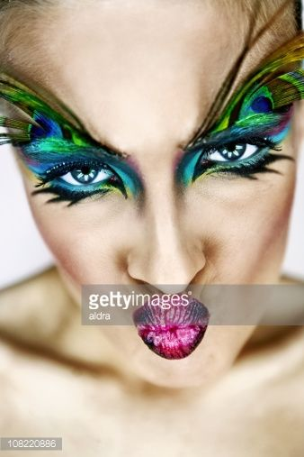 Photo of Stock Photo: Young woman with makeup and peacock feather on eyebrows