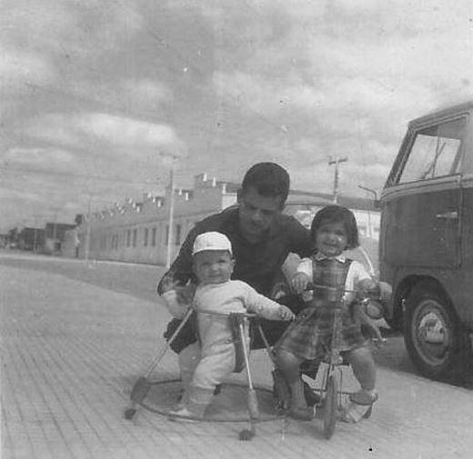 rua Eugenio Moreira, quase na esquina com rua Paraná, no bairro Bucarein, em Joinville. Ao fundo, aparece o prédio, que já não existe mais, da Companhia Hansen Industrial. As pessoas na foto são Luiz Carlos de Campos (Cacau) com os filhos Dorval e Simone.