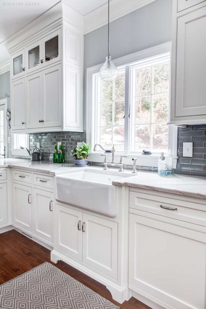 White farmhouse sink with subway tile backsplash and hard maple ...