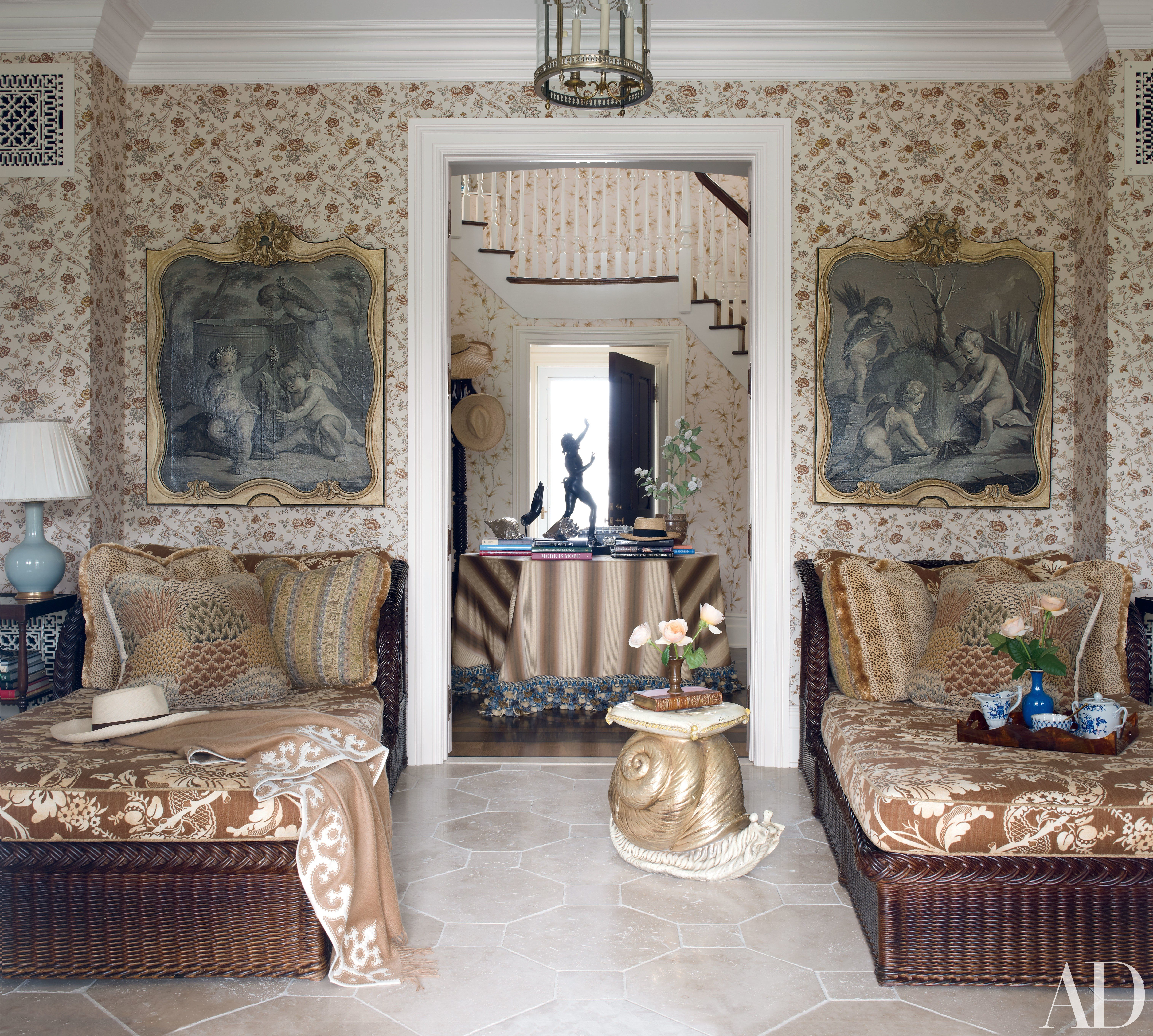 At decorator Alex Papachristidis's Bridgehampton, New York, home, a loggia's Cowtan & Tout wall covering serves as a backdrop for two 18th-century grisaille paintings, each hanging above a Bielecky Brothers wicker daybed with cushions of a Clarence House fabric.