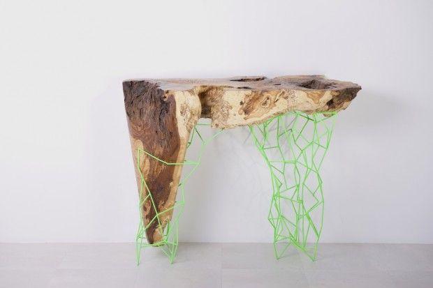 L'artiste a utilisé des troncs centenaires d'oliviers morts pour réaliser les plateaux de ses consoles uniques, équipées chacune d'un pied de métal au design filaire qui donne l'impression d'une extension informatique supportant le bois.
