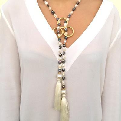 d2b25978fe9d Collar largo y abierto de perlas de rio blancas irregulares rematado en los  extremos con dos borlones y con triángulo de zamak bañado en oro mate