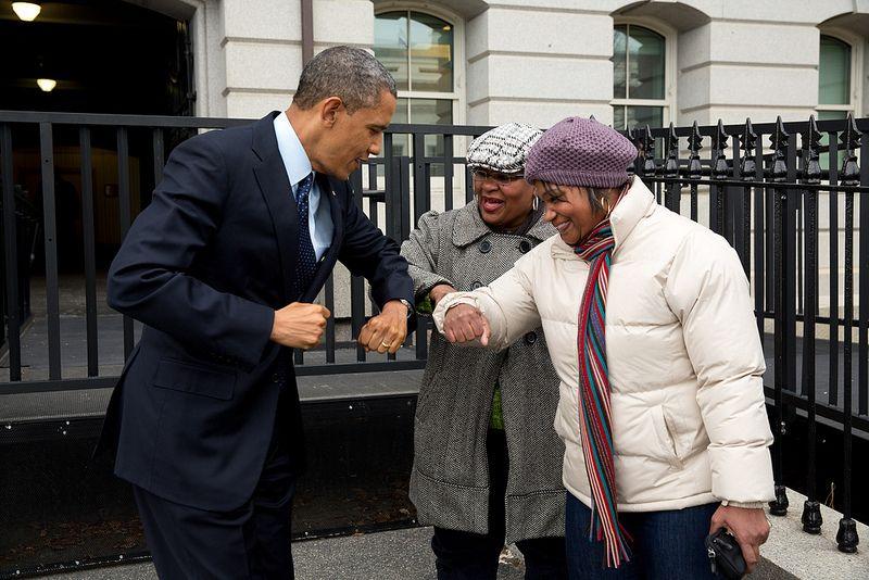 31-12-2012 - De president begroet twee welzijnswerksters op straat. Omdat hij juist crème op zijn handen smeerde, geeft hij de vrouwen een 'elleboogstoot'.
