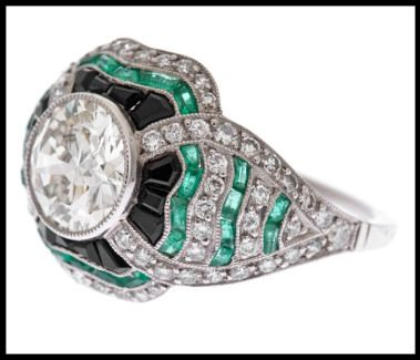 Side detail: Art Deco-style diamond, emerald, and onyx ring. Via Diamonds in the Library.