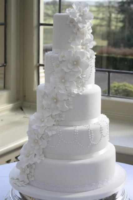5 tier round white wedding cake with white flowers draping down