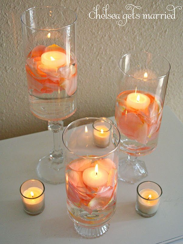 DIY centerpieces for the reception!  I put real light pink rose petals in water, followed by a floating candle in each hurricane.