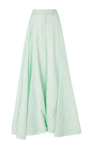 Part of New York fashion's new guard, the designer is known for her sly, surrealist aesthetic. These **Rosie Assoulin** pants feature an exaggerated flared leg in mint green seersucker fabrication.