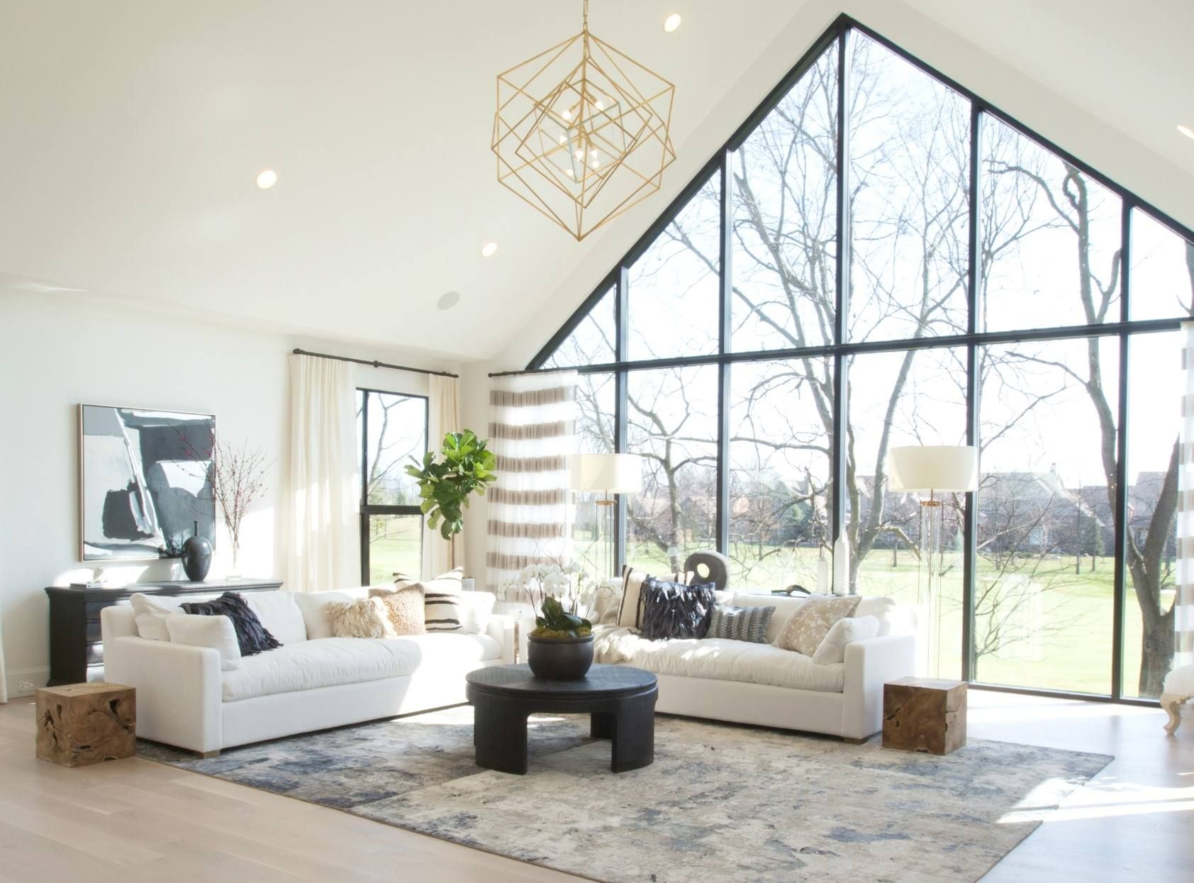 neutral textural living room Black metal windows and white sofas