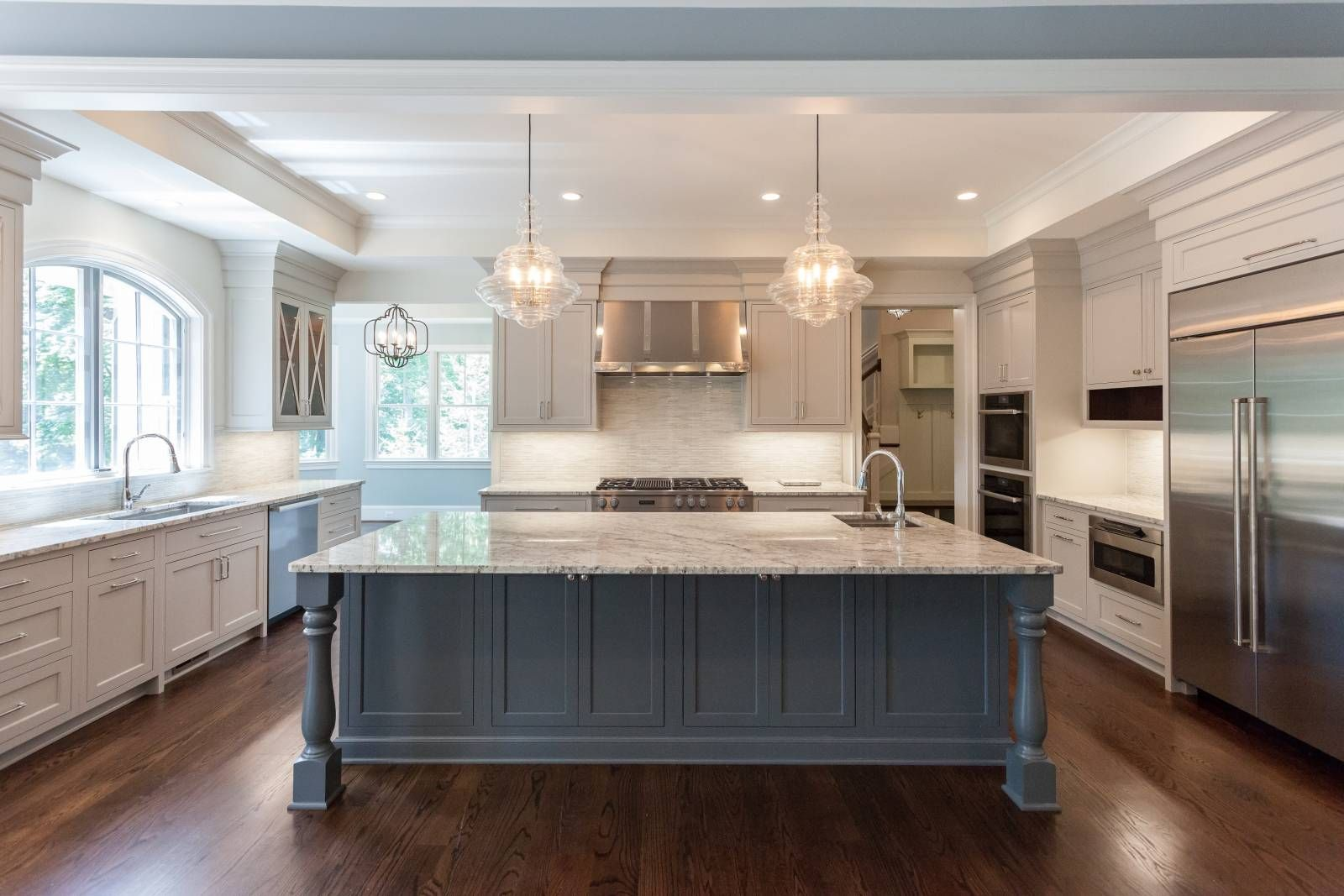 Kitchen With Contrast Gray Island And Beige Cabinets Featuring Arched Windows And Ribbed Stainless Steel Ra Beige Kitchen Beige Kitchen Cabinets Beige Cabinets