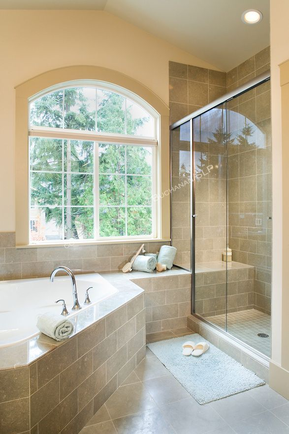 A roomy master bathroom suite with a raised deck corner tub, walk-in ...