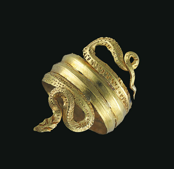 A GREEK GOLD SNAKE RING LATE HELLENISTIC PERIOD, CIRCA 1ST CENTURY B.C. Formed from a sheet strap, carinated on the exterior, wound into a three-coil spiral, the tail curving back and looped, the head turned out, forming an S, with stippled and incised details indicating the scales 1 in. (2.5 cm.) wide