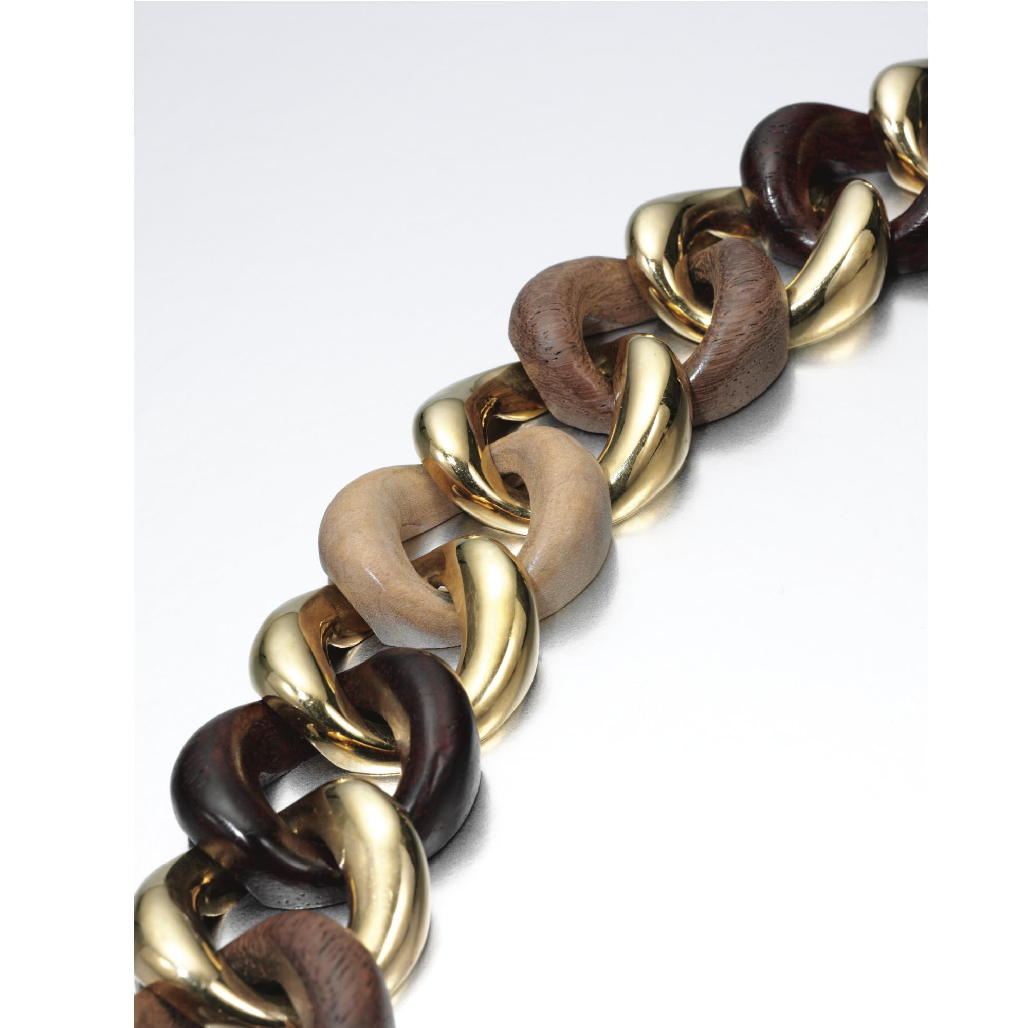 WOOD AND YELLOW GOLD LINK BRACELET, SEAMAN SCHEPPS Designed as a line of interlocking curb links of polished yellow gold and wood, signed Seaman Schepps and numbered, maker's marks. length approximately 195mm,
