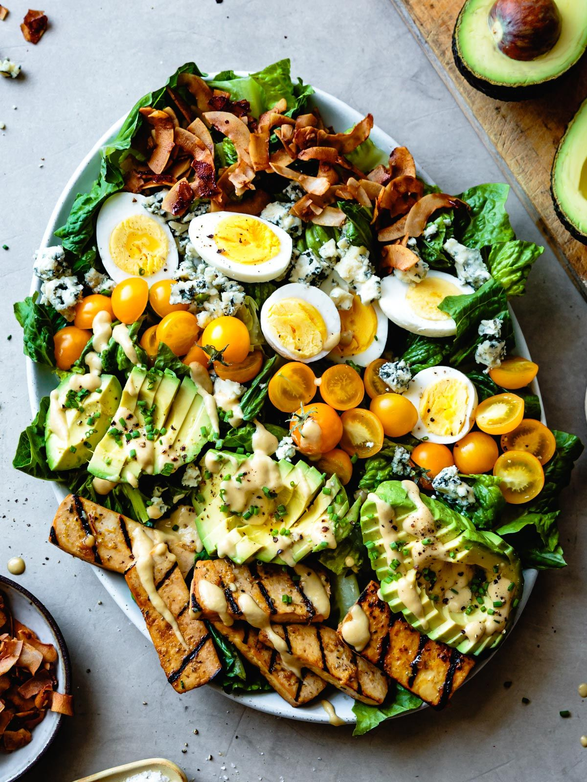 Protein-packed vegetarian Cobb salad loaded with grilled tofu, coconut bacon, avocado, tomatoes, eggs, blue cheese, and creamy mustard vinaigrette.
