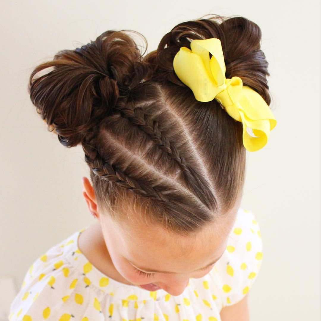 I little girl double messy buns added a couple braids and a bow