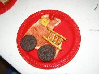 The truck is a piece of bread with a square cut out of the top. Its covered with strawberry jam. The window is a Cheezit. The ladder is made of pretzels. The wheels are Oreo cookies with the creme filling removed. The light on top is a cherry.