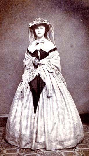 1860s silk skirt worn with velvet Swiss waist and fine white blouse underneath, hat w/veil, parasol and shawl