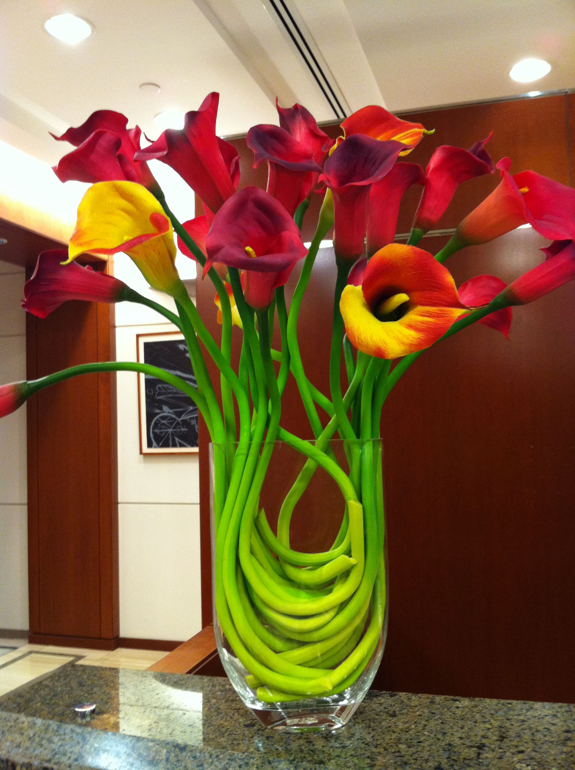 If these were white calla lilies i would like it even more the red orange and yellow calla lily arrangement dhlflorist Images