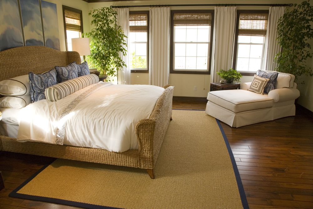 natural wood panel hard flooring here sets off the wicker bed frame and off white lounge chair and bedding master bedrooms pinterest master bedrooms