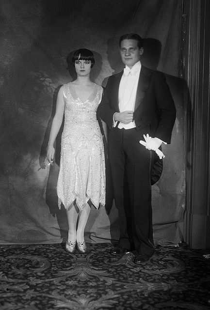 15 Nov 1923, New York--- Many national stage favorites appeared at the now famous Actor's Equity Ball at the Hotel Astor, New York City, displaying the most costly and brilliant of gowns. Shown is John W. Harkrider with Louise Brooks who is wearing a gown of satin trimmed with black and white crystal rhinestones