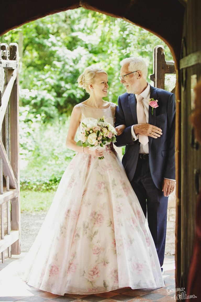 bride in floral wedding dress waits at church door with her father ...